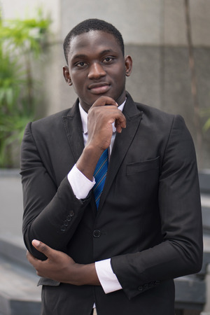 confident african businessman thinking; portrait of confident, thoughtful african or business man, manager, CEO thinking, planning, finding good idea; young adult african man model Stock Photo