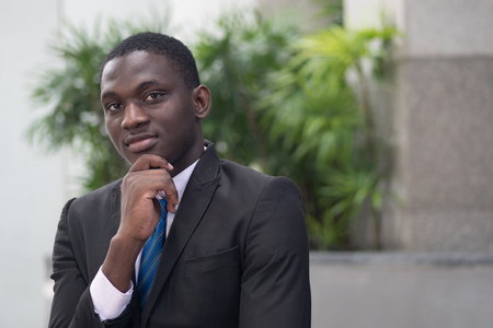 confident african businessman thinking; portrait of confident, thoughtful african business man, manager, CEO thinking, planning, finding good idea; young adult african man model
