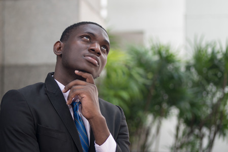 confident african or black businessman thinking; portrait of confident, thoughtful african or black business man, manager, CEO thinking, planning, finding good idea; young adult african man model