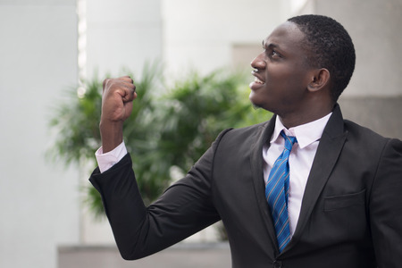 confident winning african businessman; portrait of successful confident african business man, manager, business executive winner being happy with success; young adult african man model