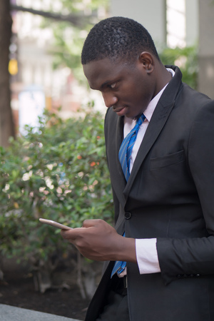 african business man using smartphone; portrait of businessman working with this smartphone, concept of mobile device technology, internet telecommunication; young adult african man model