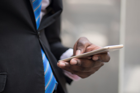 african business man hand using smartphone; hand of businessman working with this smartphone, concept of mobile device technology, internet telecommunication; young adult african man hand model Stock Photo