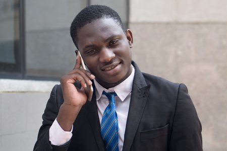 african business man using smartphone; portrait of serious businessman thinking, talking via his smartphone, concept of technology, mobile device, internet; young adult african man model
