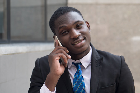 african business man using smartphone; portrait of confident happy smiling businessman talking via his smartphone, concept of success deal; young adult african man model