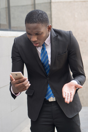 upset african business man using smartphone; portrait of upset, unhappy, angry, frustrated businessman talking via his smartphone, concept of success deal; young adult african man model Stock Photo