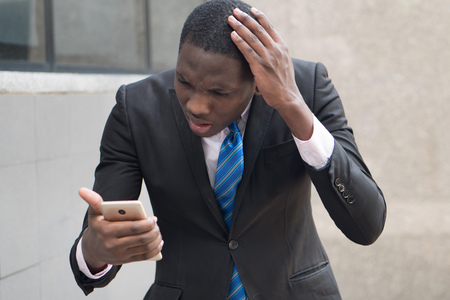 upset african business man using smartphone; portrait of upset, unhappy, angry, frustrated black businessman talking via his smartphone, concept of success deal; young adult african man model
