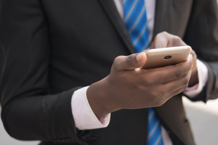 african business man hand using smartphone; hand of black businessman working with this smartphone, concept of mobile device technology, internet telecommunication; young adult african man hand model