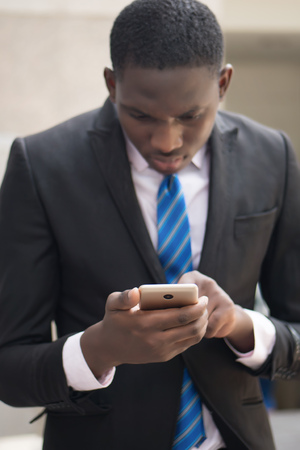 african business man using smartphone; portrait of black businessman working with this smartphone, concept of mobile device technology, internet telecommunication; young adult african man model