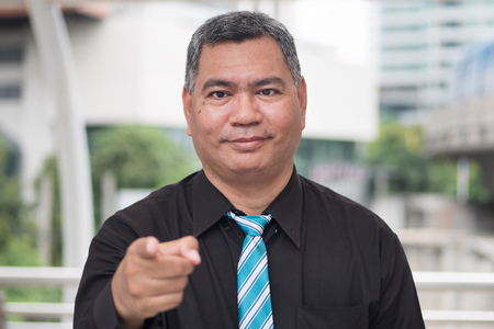 old business man pointing up at you, job recruit concept; portrait of confident, successful asian business man pointing finger or pointing hand at camera; 50s old south east asian man model