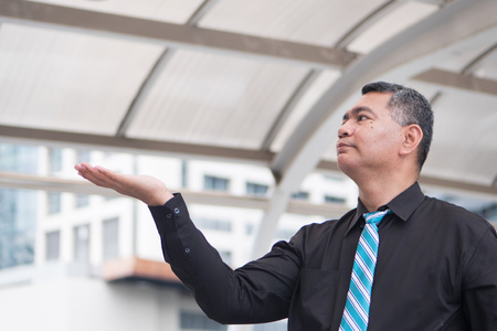 old business man pointing up, showing, presenting concept; portrait of confident, successful asian business man pointing finger or pointing hand up to blank space; 50s old south east asian man model