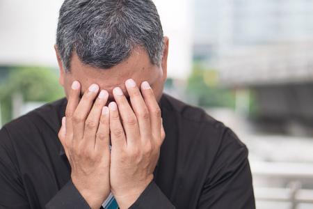 sick old senior man suffers from headahce; portrait of stressed, serious, sick old asian senior man with headache, migraine, vertigo, dizziness, stress, overwork; south east asian old senior man model
