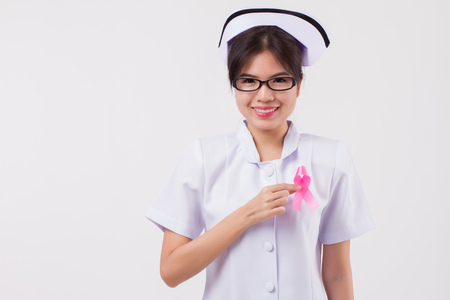 woman nurse hand holding pink ribbon bow, breast cancer awareness symbol, breast cancer day; pink ribbon for medical, nurse charity fund raising concept for breast cancer patient or prevention