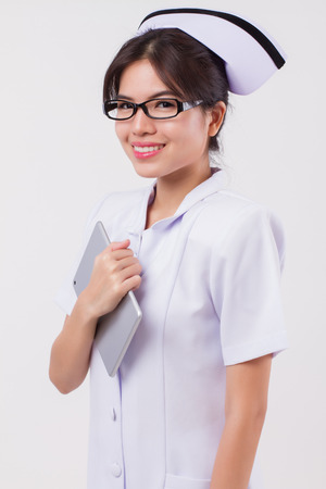 happy, smiling asian woman nurse holding computer tablet; studio isolated portrait of asian female nurse in positive, friendly, happy, smiling expression with tablet; asian 20s young adult woman model Stock Photo