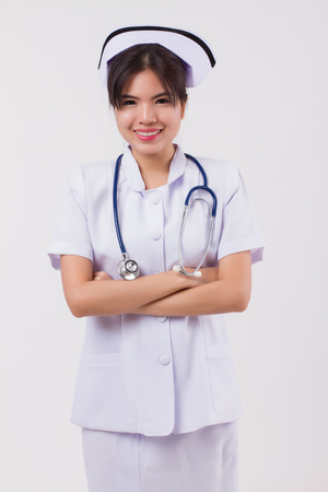 happy, smiling asian woman nurse with stethoscope; studio isolated portrait of confident asian female nurse with stethoscope for sickness or symptoms diagnosis; asian 20s young adult woman model Stock Photo