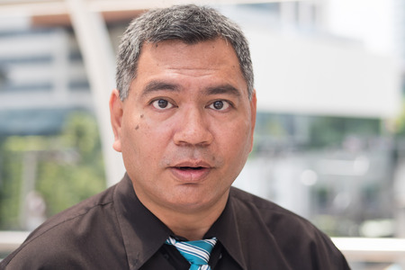 surprised old business man. portrait of excited businessman looking at you with surprise, open mouth or jaw dropping pose. southeast asian middle aged man model. Stock Photo