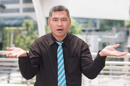surprised old business man. portrait of excited businessman looking at you with surprise. southeast asian middle aged man model.
