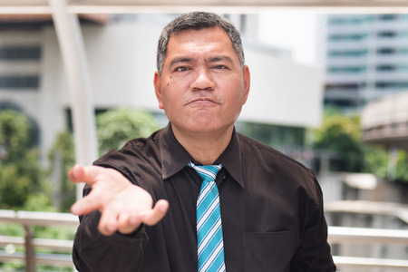 angry middle aged business man looking at you, portrait of frustrated, upset asian businessman expression. Concept of business problem, lay off, depression. southeast asian 50s old man model Stock Photo