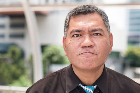angry middle aged business man looking at you, portrait of frustrated, upset asian businessman expression. Concept of business problem, unemployment, lay off, depression. asian 50s old man model Stock Photo