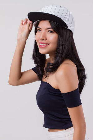 cute happy smiling woman wearing cap. portrait of positive optimistic urban woman with modern fashion, studio white isolated with friendly girl face. young adult beautiful girl asian woman model