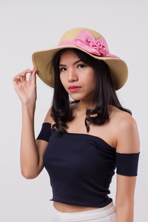 happy confident woman wearing summer travel hat. portrait of positive optimistic woman traveller, studio white isolated with holiday or vacation concept. young adult beautiful girl asian woman model