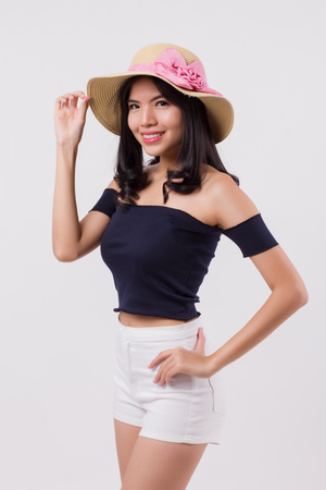 happy smiling woman wearing summer travel hat. portrait of positive optimistic woman traveller, studio white isolated with holiday or vacation concept. young adult beautiful girl asian woman model