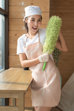 woman cleaner cleaning living room in apartment. portrait of asian woman cleaning staff doing housekeeping or domestic helper job. young adult asian woman model Stock Photo
