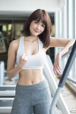 healthy strong fitness woman working out in gym. portrait of fitness woman in gym posing for strong body, gym workout, fitness people, healthy lifestyle concept. asian adult fitness woman model Stock Photo