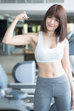 healthy strong fitness woman works out in gym. portrait of fitness woman in gym posing for strong body and arm, gym workout, weight training, healthy lifestyle concept. asian adult fitness woman model