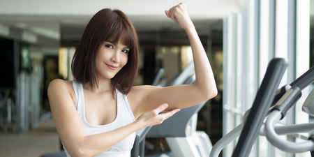 healthy strong fitness woman works out in gym. portrait of fitness woman in gym posing for strong body and arm, gym workout, weight training, healthy lifestyle concept. panorama banner crop format Stock Photo