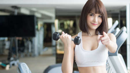 healthy strong fitness woman looking and pointing at you. portrait of fitness woman in gym posing for gym workout, looking and pointing to invite you to join the club. asian adult fitness woman model