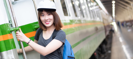 woman travels on train; portrait of asian woman traveler catching the train on train station platform; vacation travel, happy traveler or holiday concept; woman 20s adult model, banner crop format