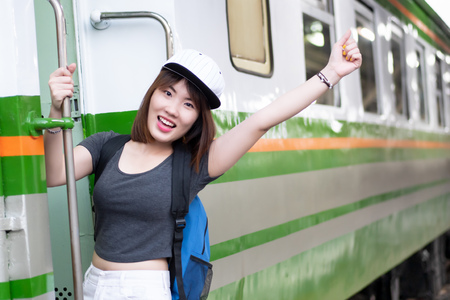 woman travels on train; portrait of asian woman traveler catching the train on train station platform, vacation travel or holiday concept; asian woman 20s adult model