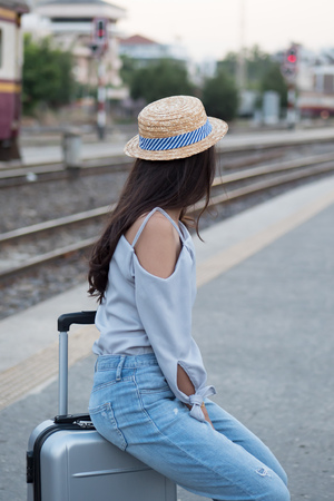 woman traveler at train station; portrait of asian woman traveler waiting train ride at train station platform; vacation, solo travel or holiday alone concept; woman 20s adult model Stock Photo