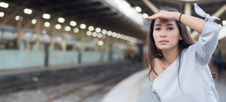 woman travels on train; portrait of asian woman traveler boarding train in train station; vacation, traveler or holiday concept; woman 20s adult model