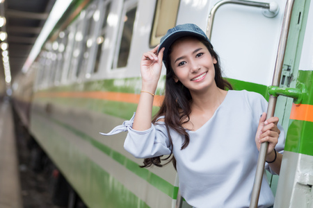 smiling happy woman travels on train; portrait of asian woman traveler boarding train in train station; vacation, happy traveler or holiday concept; woman 20s adult model Stock Photo