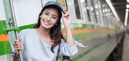 smiling happy woman travels on train; portrait of asian woman traveler boarding train in train station; vacation, happy traveler or holiday concept; woman 20s adult model, banner crop format