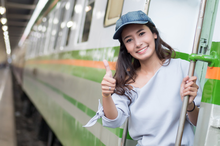 smiling happy woman travels giving thumb up gesture; portrait of asian woman traveler boarding train; good vacation, happy traveler, pleasant holiday concept; woman 20s adult model Stock Photo