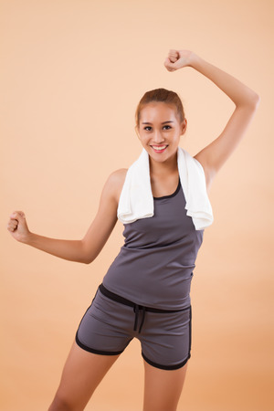 happy smiling asian woman doing fitness aerobic exercise; portrait of woman fitness training, yoga, warm up workout, exercising, dancing for healthy lifestyle concept; tan skin asian woman model 写真素材 - 118045135