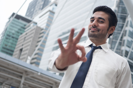 asian business man pointing ok gesture; portrait of Asian, north indian successful and confident businessman points his approving, yes, ok or okay hand sign