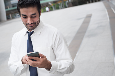 happy asian business man using smart phone; portrait of happy smiling successful Asian, north indian businessman using smart phone for app, internet connection, good connection concept
