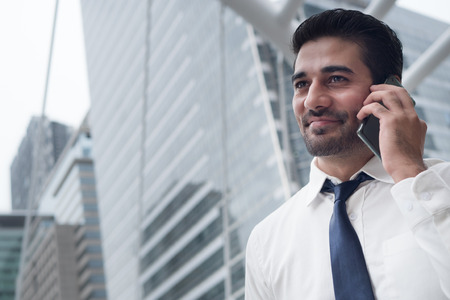 happy asian business man talking smart phone; portrait of happy smiling successful Asian, Indian businessman talking via smart phone; negotiation, business deal, transaction, communication concept Stock Photo