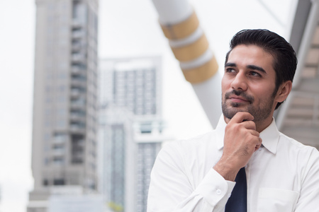 thoughtful asian business man thinking and looking up; portrait of Asian, north indian successful and confident businessman thinking, planning, looking, having future project