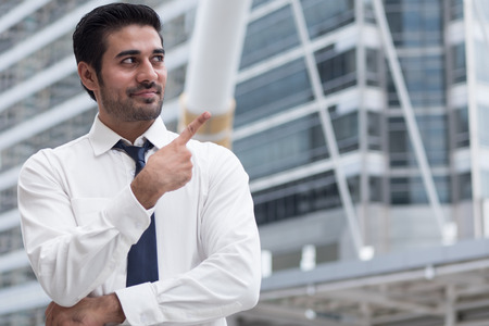 asian business man pointing up; portrait of Asian, north indian successful and confident businessman points his finger up Stock Photo