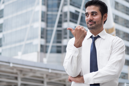 asian business man pointing thumb up gesture; portrait of Asian, north indian successful and confident businessman points his approving, yes, ok thumb up