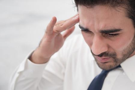 depressed asian business man; portrait of sick indian asian man with depression suffering from headache, vertigo, hangover, migraine, stress Stock Photo