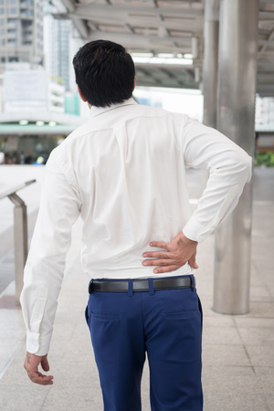 Sick unhealthy asian man suffering from back pain, spine problem, hernicated disc, spinal disc dislocation or displacement, office syndrome