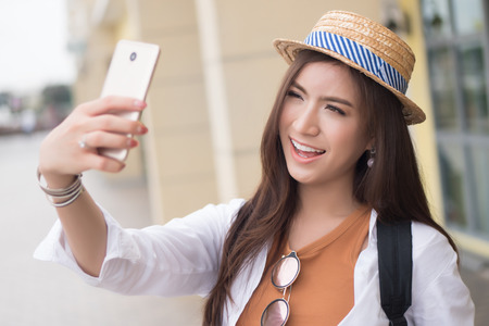 Asian woman traveler taking photo of travel destination; portrait of happy laughing Chinese Asian woman tourist shooting photograph or video with smartphone; holiday, vacation, travel, tourism concept Stock Photo