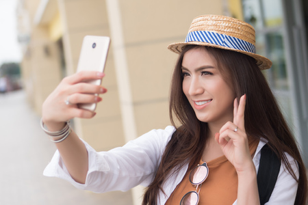 Asian woman traveler taking photo of travel destination; portrait of happy smiling Chinese Asian woman tourist shooting photograph or video with smartphone; holiday, vacation, travel, tourism concept