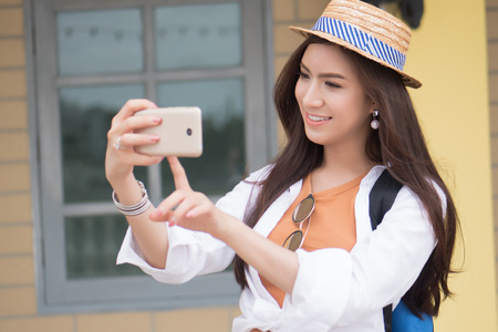 Asian woman traveler taking photo of travel destination; portrait of happy surprised excited Chinese Asian woman tourist shooting photograph with smartphone; holiday, vacation, travel, tourism concept
