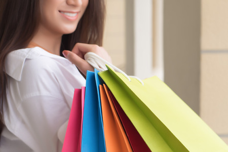 shopping asian girl; portrait of exited, surprised, happy smiling woman shopper; Asian Chinese woman holding shopping bag, concept of sale, travel and shopping, consumer, good economic